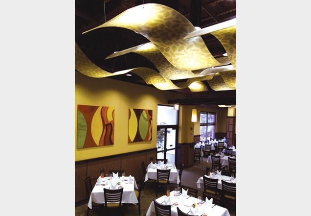 Curved ceiling panels with an interlayer of green leaves.